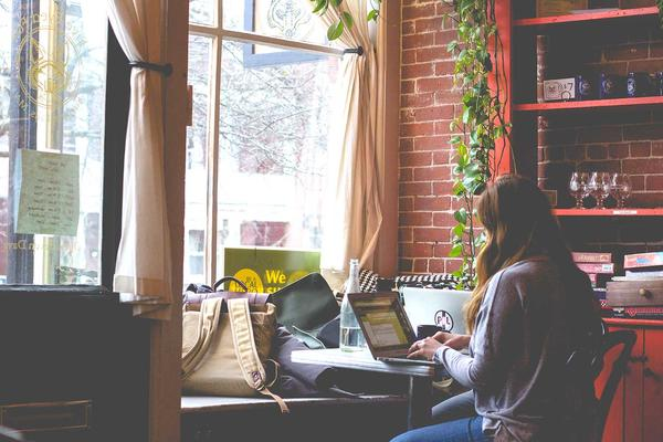 a female student working on her laptop in a cafe. Photo byBonnie Kittleon Unsplash.