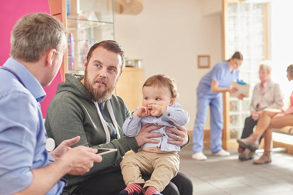 GP holding a tablet computer interviews a father with a baby in the waiting room, in the background a practice nurse shows notes to two patients. Photo iStock.