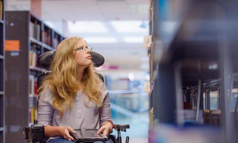 student in a wheelchair with a tablet computer looks at library shelves photo by istock